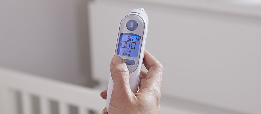 Hand holding up Braun thermometer