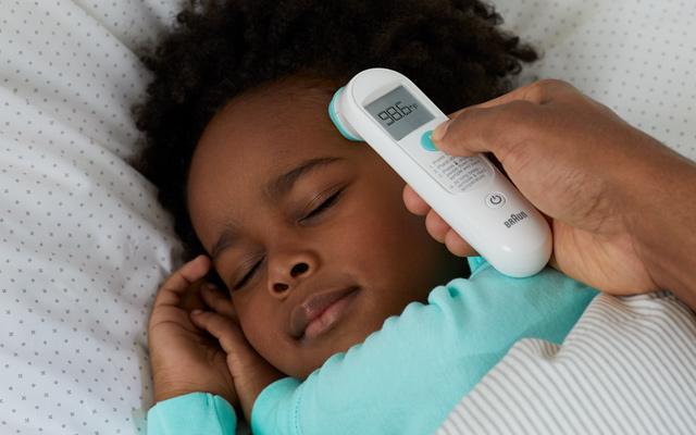 parent checking child's forehead temperature