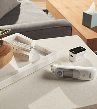 Braun thermometer and pulse oximeter on coffee table