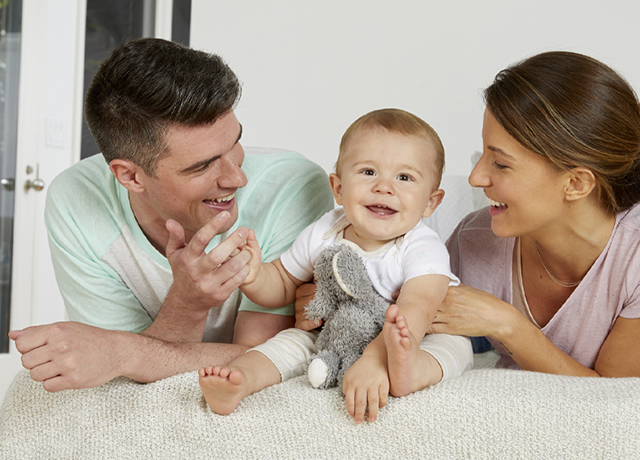 happy family sitting with smiling baby